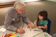 A volunteer helps a young visitor make a leaf for the memory tree.
